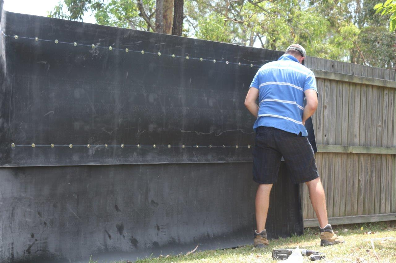 A man in a blue striped shirt installing an acoustic fence wrap on his backyard fence