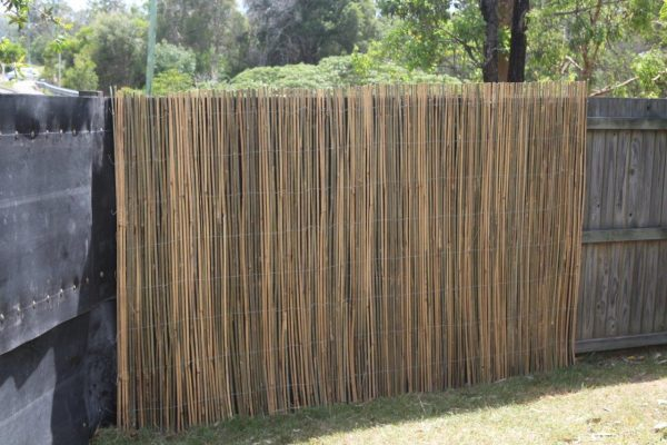 A bamboo fence wrap being installed on top of an acoustic fence wrap in a backyard